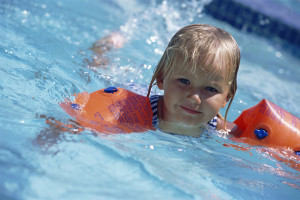 Young Girl Swimming with Water Wings
